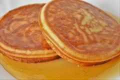 Crepes con la miel en un platillo blanco Imágenes de archivo libres de regalías
