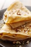Crepes con la miel o jarabe y tuercas asadas Imágenes de archivo libres de regalías