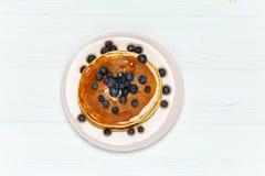Crepes con la miel y los arándanos aislados en el fondo blanco Imagen de archivo