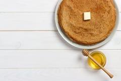 Crepes con la miel y la mantequilla en un fondo de madera Foto de archivo libre de regalías