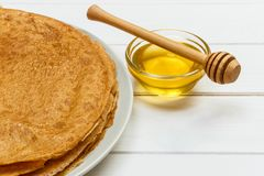 Crepes con la miel y la mantequilla en un fondo de madera Imagenes de archivo