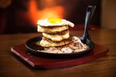 Crepes con la salchicha y los huevos revueltos en un sartén Fotografía de archivo libre de regalías