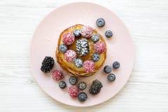 Crepes con las bayas, la miel y el azúcar en una placa rosada sobre el fondo de madera blanco, visión superior Fotografía de archivo libre de regalías