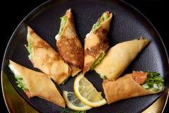 Crepes con las rebanadas del relleno y del limón en un plato imagen de archivo
