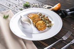 Crepes con las setas y las cebollas fritas Crepes de patata con las setas y la crema agria Cocina ucraniana, europea Imagen de archivo
