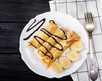 Crepes con requesón y un plátano con el jarabe de chocolate Foto de archivo