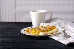 Crepes con requesón y un plátano con el jarabe de chocolate Fotografía de archivo libre de regalías