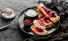 Crepes with cottage cheese, fruit jam, cherries, sour cream and icing sugar on black plate over dark background. Top view, flat. Lay. Pancake week or Shrovetide royalty free stock photography