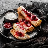 Crepes with cottage cheese, fruit jam, cherries, sour cream and icing sugar on black plate over dark background. Top view. Flat lay. Pancake week or Shrovetide stock photo