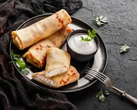 Crepes with cottage cheese, greens and sour cream on black plate over dark background. Pancake week or Shrovetide. Healthy breakfast. Top view, flat lay stock photography