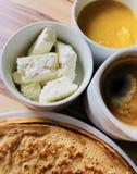 Crepes de la comida con el queso blanco de la miel local de la abeja en foco y negro sin café de las cucharas Foto de archivo