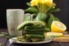 Crepes de la espinaca en la tabla de madera y la primavera amarilla Imagen de archivo libre de regalías