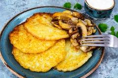 Crepes de patata caliente con las setas fritas Fotos de archivo