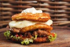 Crepes de patata deliciosas de la hamburguesa con la carne, lechuga, queso, tomates en el tablero de madera Imagen de archivo