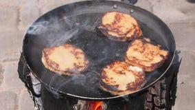 Crepes de patata, fritas frito en una cacerola sobre un fuego abierto almacen de video