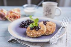 Crepes del queso cuajado, pasteles de queso para el desayuno con las bayas y crema agria Fotos de archivo libres de regalías