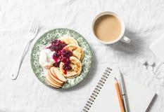 Crepes del requesón con la salsa griega del yogur y de arándano, café con la leche, cuaderno, teléfono con los auriculares en la  Foto de archivo