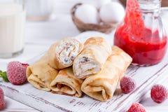 Crepes del rollo con requesón y bayas La idea para un desayuno Foto de archivo