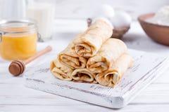 Crepes del rollo con requesón y bayas La idea para un desayuno Fotos de archivo