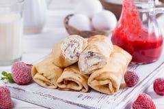 Crepes del rollo con requesón y bayas La idea para un desayuno Imagenes de archivo