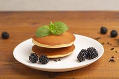 Crepes deliciosas con Blackberry y la menta, en una placa blanca imagen de archivo