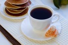Crepes deliciosas con la miel y una taza de café en una etiqueta blanca Foto de archivo