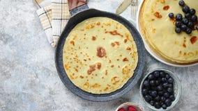 Crepes deliciosas en el sartén de piedra Colocado en la tabla con los diversos ingredientes