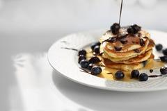 Crepes dulces del desayuno con los ar?ndanos y el jarabe de arce fotografía de archivo
