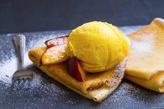 Crepes fiiled с вареньем, кусками персика и ветроуловителем мороженого на верхней части Стоковое Фото