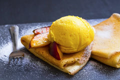 Crepes fiiled with jam, peach slices and ice cream scoop on top. With powdered sugar, sweet fruits dessert Stock Photo