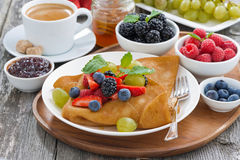 Crepes with fresh berries and honey, coffee for breakfast Stock Image