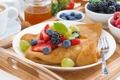 Crepes with fresh berries and honey on a plate. Close-up royalty free stock photos