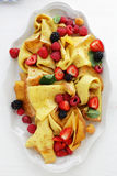 Crepes with fresh berries on white plate. Food above Stock Images
