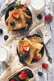 Crepes with fresh raspberry and blackberry. And cups of milk Royalty Free Stock Photo