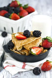 Crepes with fresh raspberry and blackberry. In small frying pan Stock Photos
