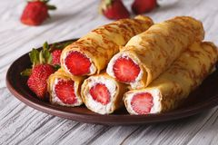 Crepes with fresh strawberries and cream cheese on a plate Stock Photos