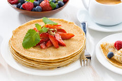 Crepes with fresh strawberry, jams and honey on white table Royalty Free Stock Photography