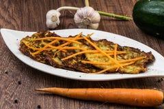 Crepes fritas del calabacín y de patata Sazonado con ajo e hierbas Zanahorias ralladas adornadas Foto de archivo libre de regalías