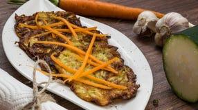 Crepes fritas del calabacín y de patata Sazonado con ajo e hierbas Zanahorias ralladas adornadas Imagen de archivo
