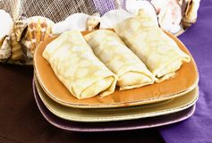 Crepes On Golden Plate. Crepes And Golden Plate On Brown And Purple Table Linen Stock Photography