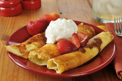 Crepes. Golden crepes with strawberries and whipped cream Royalty Free Stock Images