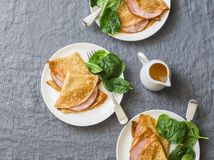 Crepes with ham and spinach. Delicious, nourish breakfast on a grey background. Top view royalty free stock photo