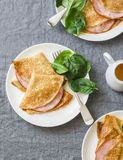 Crepes with ham and spinach. Delicious, nourish breakfast or snack on a grey background. Top view royalty free stock photography