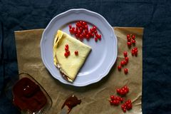 Crepes. Homemade crepes with chocolate spread and red currants. Top view royalty free stock photography