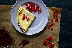 Crepes. Homemade crepes with chocolate spread and red currants. Top view stock image