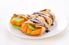 Crepes with kiwi and apricot slices. On white plate Royalty Free Stock Photo