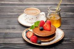 Crepes, miel, bayas y una taza de café express del café imagen de archivo libre de regalías