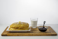 Crepes with milk and black currant jam on wood royalty free stock photography