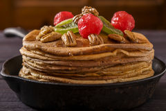 Crepes with nuts and candied fruits. On a dark wooden background Royalty Free Stock Photography