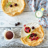 Crepes (Pancakes) with berries. Breakfast: crepes with cherry and raspberry, sour cream and hot tea Royalty Free Stock Images